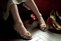 窓辺に座るサンダルを履いた女性の足元とヒール靴