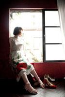 窓辺に座ったスカートをはいている女性とヒール靴