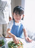 サラダを持つ女の子とお母さん