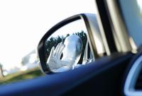 自動車のサイドミラーに写るシルバーボディースーツでコスプレした人