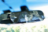 自動車のバックミラーに写るシルバーボディースーツでコスプレした人