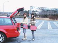 スノーボードを持つ2人の日本人女性と車
