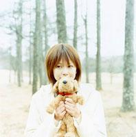 縫いぐるみを持つ日本人女性と木々