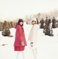 雪を歩く2人の日本人女性と木々