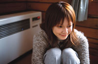 座る日本人女性と暖房