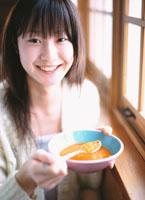 窓辺でスープを持つ日本人女性