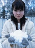 雪を手に載せる日本人女性