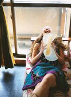ソファで帽子を持つ日本人女性