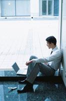 日本人ビジネスマンと携帯電話とコンピューター