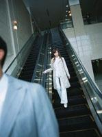 エスカレーターを下りる日本人ビジネスウーマン