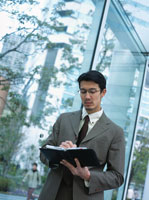 システムノートを開く日本人ビジネスマン