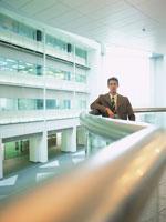 手すりにもたれる日本人ビジネスマン 02299000460| 写真素材・ストックフォト・画像・イラスト素材|アマナイメージズ