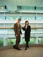 手すりにもたれる日本人ビジネスマン&ウーマン