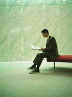 ソファーで新聞を読む日本人ビジネスマン