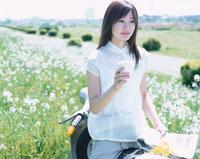 単車に乗りコーヒーを持つ日本人女性