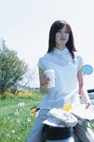 単車に乗りコーヒーを持つ日本人女性 02299000529| 写真素材・ストックフォト・画像・イラスト素材|アマナイメージズ