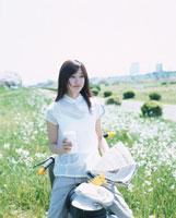 単車に乗りコーヒーを持つ日本人女性 02299000531| 写真素材・ストックフォト・画像・イラスト素材|アマナイメージズ