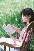 屋外の椅子に座り本を読む日本人女性