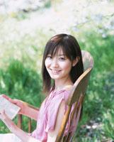 草原の中の椅子に座り本を読む日本人女性