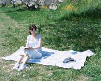 シートに座って本を読む日本人女性と帽子と桜