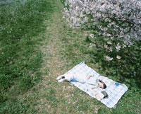 シートに寝転ぶ日本人女性と桜