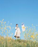 バス停で携帯電話で話す日本人女性と花