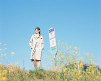 バス停で待つ日本人女性と黄色の花