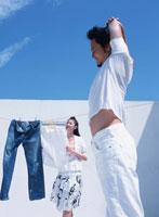 ストレッチをする日本人男性と洗濯物を干す女性
