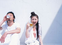 白壁にもたれてビールを飲む日本人カップル