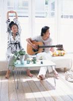 伸びをする日本人女性とギターを弾く男性