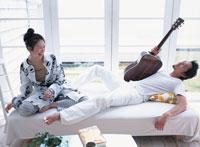 日本人女性とギター持って寝転ぶ男性