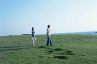 海岸の芝生を歩く日本人カップル