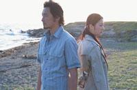 海岸で背中合わせで立つ日本人カップル