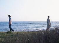 海岸で背を向けて歩く日本人カップル 02299000878| 写真素材・ストックフォト・画像・イラスト素材|アマナイメージズ