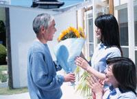 花束を渡す祖父 02299000930  写真素材・ストックフォト・画像・イラスト素材 アマナイメージズ