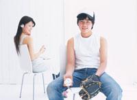 ヘッドフォンをあてる女性と野球グローブの男性