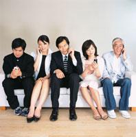 携帯電話を操作する家族 02299001026  写真素材・ストックフォト・画像・イラスト素材 アマナイメージズ