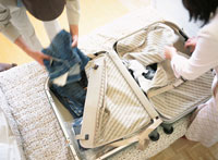 スーツケースに衣服を積める日本人男性と女性