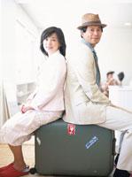 背中合わせでスーツケースに座る日本人夫婦