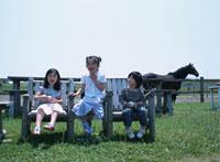 牧場のベンチに座る3人の日本人の子供