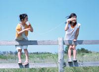 草原の柵につかまり糸電話で遊ぶ2人の日本人の女の子 02299001110| 写真素材・ストックフォト・画像・イラスト素材|アマナイメージズ