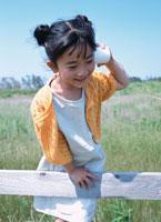 柵につかまり糸電話で遊ぶ日本人の女の子 02299001114| 写真素材・ストックフォト・画像・イラスト素材|アマナイメージズ