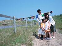 草原で寄り添う日本人家族 02299001117| 写真素材・ストックフォト・画像・イラスト素材|アマナイメージズ