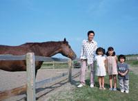 牧場の馬と父親と3人の子供たち
