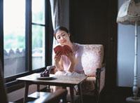 窓辺で読書する日本人女性