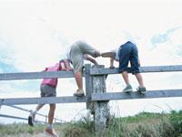 柵を越える3人の男の子の後姿 日本人