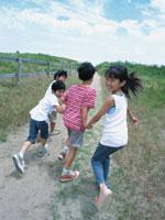 手をつないで走り出す男の子と女の子 日本人