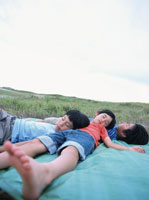 芝生に敷いたシートの上で寝る子供たち 日本人