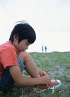 靴の紐を結ぶ日本人の男の子