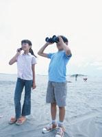 双眼鏡を覗く男の子と携帯電話で話す女の子 日本人